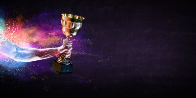Fototapeta Hand holding up a gold trophy cup against dark background