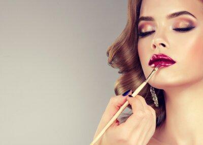 Fototapeta Hand of make-up pána, malovat rty mladé krásné modelu. Make-up Probíhá.