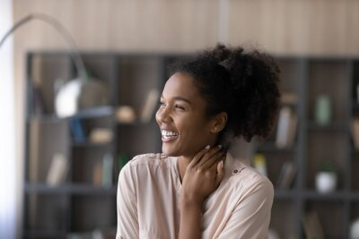 Fototapeta Head shot excited happy dreamy African American woman looking to aside, visualizing good future, overjoyed attractive young female dreaming about new opportunities, having fun, laughing at joke