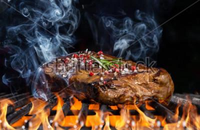 Fototapeta Hovězí steak na grilu v ohni s černým pozadím