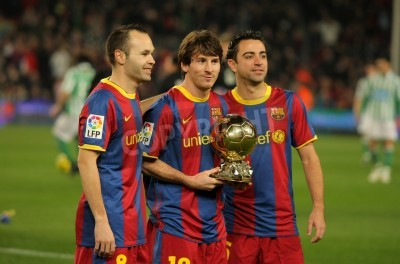 Fototapeta Iniesta, Messi and Xavi of Barcelona with golden ball before a Spanish Cup match between FC Barcelona and Real Betis at the Nou Camp Stadium on January 12, 2011 in Barcelona, Spain
