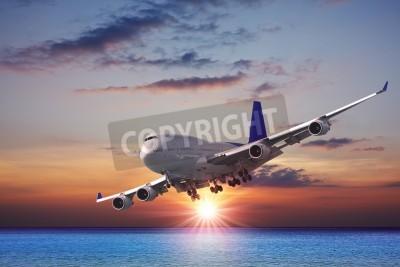 Fototapeta Jet liner over the sea at dusk