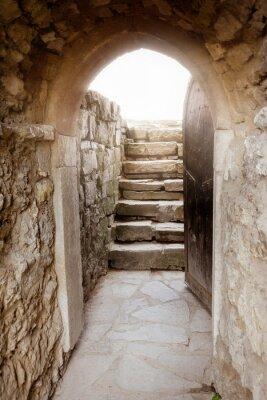 Fototapeta Kamenná zeď s otevřenými dveřmi a paprsky světla za