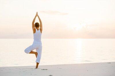 Fototapeta Kavkazský žena cvičí jógu na pobřeží