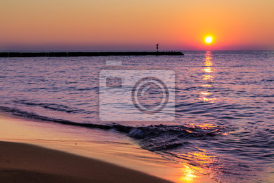 Fototapeta Klidný, vyrovnaný západu slunce u moře a jemné vlny stříkající na pláži.