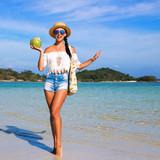 dc6f10c3af4 Krásná roztomilá šťastná dívka na pláži. oblečené v džínových šortkách