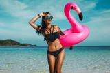 53e8616ef08 Krásná sexy úžasná mladá žena na pláži sedí na nafukovací růžový plameňák a  směje se