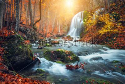 Fototapeta Krásný vodopád na horské řeky v barevné podzimní les s červenými a oranžovými listy při západu slunce. Přírodní krajina
