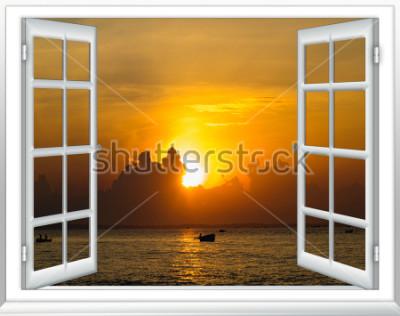 Fototapeta krásný západ slunce na výhled na moře z okna se závěsy otevřené
