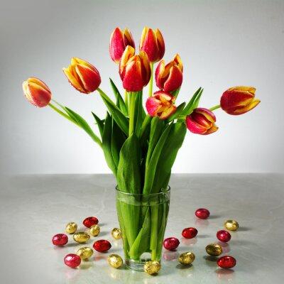 Fototapeta kytice z čerstvých tulipánů a malým červeným žluté čokolády velikonoční např