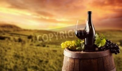 Fototapeta Láhev červeného vína a skla na dřevěném soudku. Vinice na pozadí