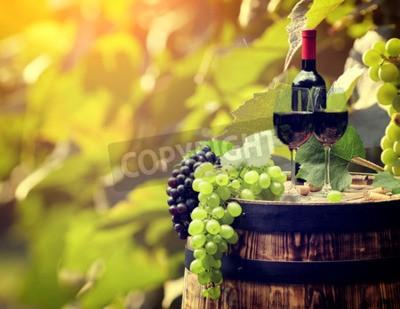 Fototapeta Láhev červeného vína a sklenice na víno na wodden barel.