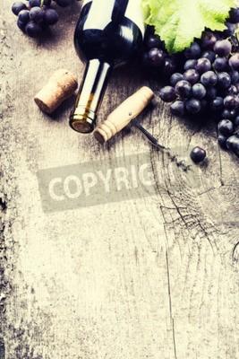 Fototapeta Láhev tmavého vína, hroznů a korky na staré dřevěné pozadí