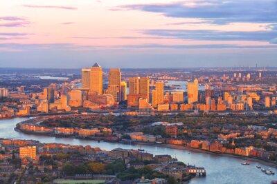 Fototapeta Letecký pohled na východ Londýnské finanční čtvrti Canary Wharf Docklands kroužil řeky Temže, s budovami osvětlené barevný západ slunce