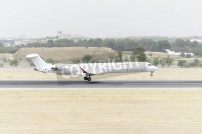 Fototapeta MADRID, ŠPANĚLSKO - 08.8.2015: Letadlo -Bombardier Canadair CRJ-900-, z -Air Nostrum- letecké společnosti, je přistání na letišti Madrid-Barajas -Adolfo Suarez-, 8. srpna 2015.