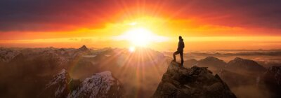 Fototapeta Magical Fantasy Adventure Composite of Man Hiking on top of a rocky mountain peak. Background Landscape from British Columbia, Canada. Sunrise Dramatic Colorful Sky