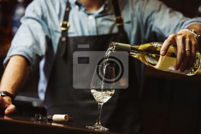 Fototapeta Male sommelier pouring white wine into long-stemmed wineglasses.