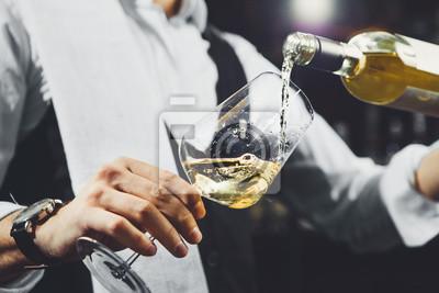 Fototapeta Male sommelier pouring white wine into wineglasses.