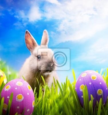 Malé velikonoční zajíček a velikonoční vejce na zelené trávě
