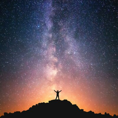 Fototapeta Man and the Universe. A person is standing on the top of the hill next to the Milky Way galaxy with his hands raised to the air.