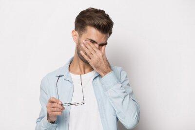 Fototapeta Man taking off glasses suffers from dry eyes studio shot