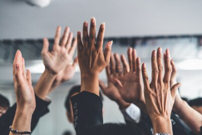 Fototapeta Many happy business people raise hands together with joy and success. Company employee celebrate after finishing successful work project. Corporate partnership and achievement concept.