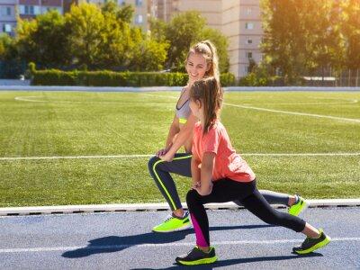 Fototapeta Matka a malá dcera se dělá cvičení na stadionu. On