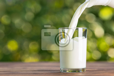 Fototapeta milk from jug pouring into glass
