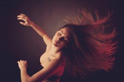 Fototapeta Mladá černovláska kavkazského žena tančí a vlasy proudící vzduch