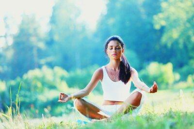 Fototapeta Mladá žena, která dělá cvičení jógy v zeleném parku