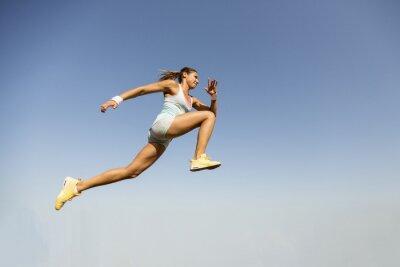 Fototapeta Mladá žena s skok do dálky