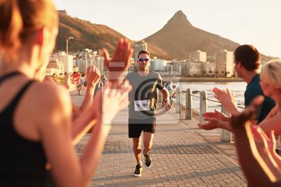 Fototapeta Mladí lidé podporující běžce na cílové čáře