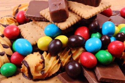 Fototapeta Mnoho sladkostí na dřevěný povrch, nezdravé jídlo