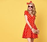 Modní pinup model girl v červené polka dots letní šaty. stylový kudrnatý  účes c7bb5d2208