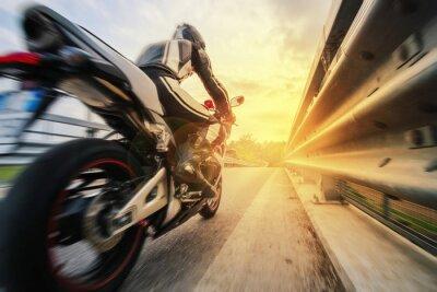 Fototapeta Moto da strada sfreccia Vicino al zábradlí al tramonto