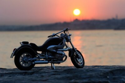 Fototapeta Motocykl na skalách v západu slunce a zlaté hodiny
