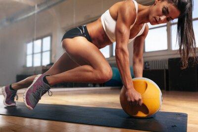 Fototapeta Muscular woman doing intense core workout in gym