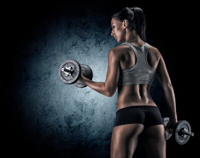 Fototapeta Muscular woman in studio on dark background
