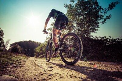 Fototapeta Muž na koni na špinavé silnici na horském kole