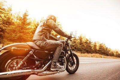 Fototapeta Muž sídlo na motocyklu na lesní cestě.