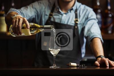 Fototapeta Muž sommelier nalévání bílého vína do skleničky s dlouhým stonkem.
