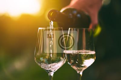 Fototapeta Nalil bílé víno do sklenic při západu slunce