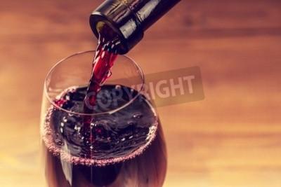 Fototapeta Nalil červené víno do sklenice proti dřevěné pozadí