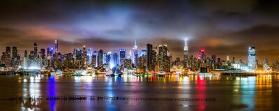 Fototapeta New York City Panorama on a cloudy night as viewed from New Jersey across the Hudson River