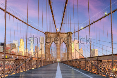 Fototapeta New York, New York on the Brooklyn Bridge Promenade facing Manhattan's skyline at dawn.