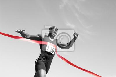 Fototapeta Nízký úhel pohledu na afro-americký mužského běžec přejezd cílové čáře proti modré obloze