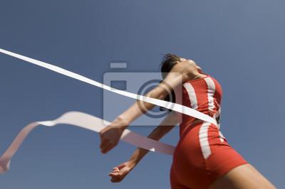 Fototapeta Nízký úhel pohledu na mladé ženy sportovce překročení cílové čáry proti jasné modré obloze