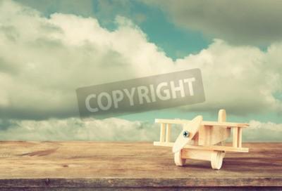 Fototapeta Obraz letadla dřevěné hračky přes dřevěný stůl proti zatažené obloze. Retro stylu obrazu