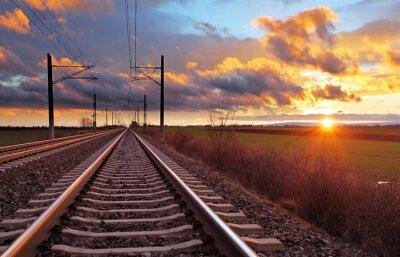 Fototapeta Oranžový západ slunce v nízkých mracích nad železnicí