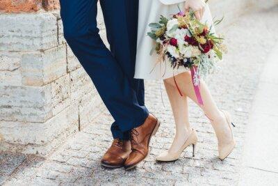 Fototapeta Oříznutý snímek krásné nevěsty na vysoké podpatky v bílých botách má pěkné kytice stojí poblíž ženicha, který nosí formální slavnostní oblek, slaví svatbu. Šťastní novomanželé. Svatební pár venkovní